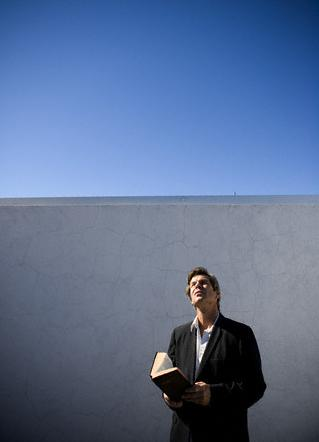Man Holding a Bible and Looking up at the Sky
